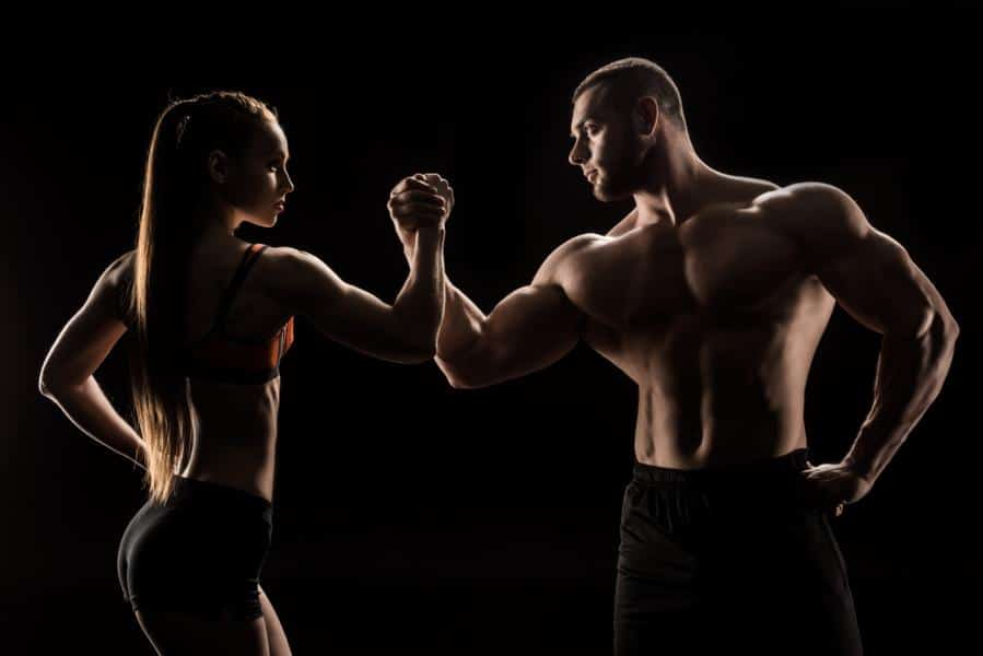 how to build muscles - young sporty couple holding hands isolated on black
